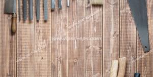عکس با کیفیت ابزارآلات نجاری آویزان بر روی دیوار و چیده شده بر روی میز چوبی از جمله اره ، انبر و قلم مو و...
