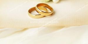 عکس با کیفیت حلقه های طلای عقد یا عروسی در کنار گل های سبز رنگ عروس و مرواریدهای سفید