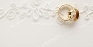 عکس با کیفیت حلقه های طلای عروس و داماد بر روی کارت عروسی با طرح برجسته
