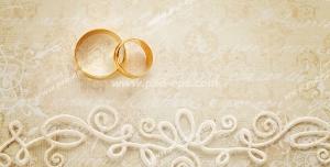 عکس با کیفیت حلقه های طلای عروس و داماد بر روی کارت عروسی طلایی رنگ با طرح برجسته