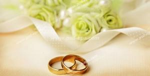 عکس با کیفیت حلقه های طلای عروس و داماد در کنار گل سبز رنگ و رمان های سفید عروس