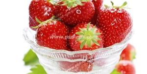 عکس با کیفیت توت فرنگی های تازه و قرمز در داخل ظرف بلوری با برگ و شکوفه آن از نمای نزدیک
