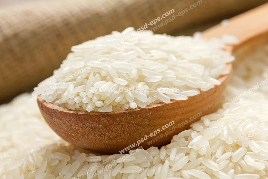 عکس با کیفیت قاشق چوبی حاوی برنج خام و پخته نشده در داخل برنج ها از نمای نزدیک