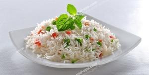 عکس با کیفیت بشقاب حاوی برنج پخته شده به همراه نخود سبز و هویج با تزئین برگ نعنا