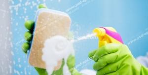 عکس با کیفیت تمیز کردن شیشه با اسفنج و شیشه شوی توسط بانویی با دستکش پلاستیکی سبز رنگ