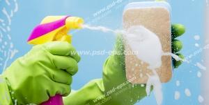 عکس با کیفیت نمایی از تمیز کردن شیشه با اسفنج و شیشه شوی توسط بانویی با دستکش پلاستیکی سبز رنگ