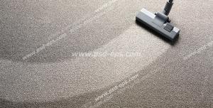 عکس با کیفیت نمایی از جارو کردن خاک روی موکت با جارو برقی