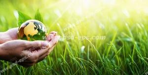 عکس با کیفیت نمادین برای روز طبیعت با کره زمین به رنگ سبز در دستان انسان در دل طبیعت سبز بهاری و چمن های روئیده در دشت