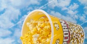 عکس با کیفیت لیوان پاپ کورن پنیری و کچاپ با زمینه آسمان آبی و ابری