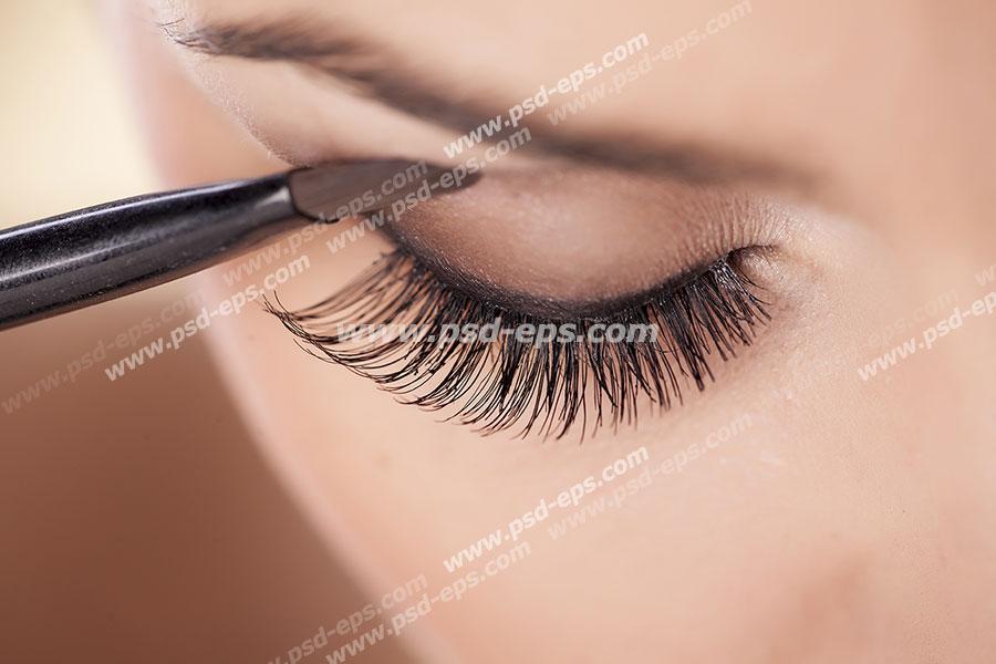 عکس با کیفیت چهره بانویی در حال میکاپ و چشم بانویی از نمای نزدیک در حال سایه زدن