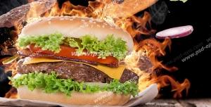 عکس با کیفیت ساندویچ همبرگر با گوجه فرنگی و کاهو و پنیر با زمینه آتش و مخلفات ساندویچ