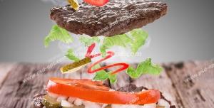 ساندویچ همبرگر با مخلفات گوجه فرنگی و خیارشور و پیاز و کاهو با زمینه خاکستری
