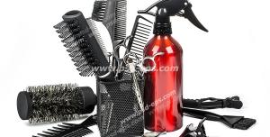 عکس با کیفیت لوازم اصلاح موی سر شامل انواع شانه و برس ها ، قیچی ، آب پاش قرمز رنگ ، چتکه رنگ با زمینه سفید