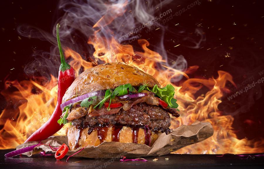 عکس با کیفیت ساندویچ همبرگر با مخلفات کاهو وفلفل قرمز و گوجه و پیاز و سس قرمز تند با زمینه آتش