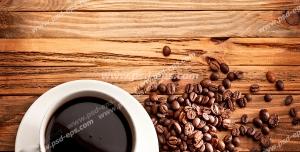 عکس با کیفیت فنجان چینی قهوه بر روی میز در کنار دانه های قهوه