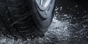 عکس با کیفیت نمای نزدیک از تایر خودرو در حال عبور از جاده در هوای بارانی