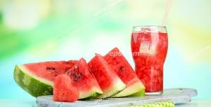 عکس با کیفیت لیوان آب هندوانه در کنار برش های هندوانه بر روی میز