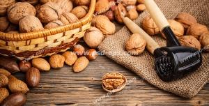 عکس با کیفیت گردوهای خشک و بادام درختی در کنار دستگاه دستی گردوشکن درون ظرف حصیری و بر روی میز