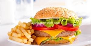 عکس با کیفیت ساندویچ همبرگر مرغ مخصوص با پنیر در کنار سیب زمینی سرخ کرده درون بشقاب چینی