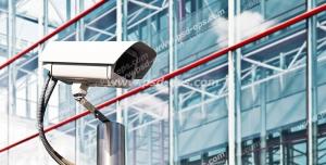 عکس با کیفیت دوربین مدار بسته نصب شده در کنار ساختمانی شیشه ای