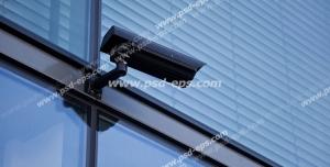 عکس با کیفیت دوربین مدار بسته مشکی رنگ نصب شده در خارج از ساختمان و در کنار پنجره