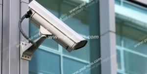 عکس با کیفیت دوربین مدار بسته سفید رنگ نصب شده بر روی ساختمان شیشه ای