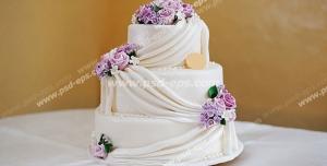 عکس با کیفیت کیک سه طبقه خامه ای تزئین شده با گل های بنفش و تورهای سفید و مروارید مناسب عروسی و نامزدی