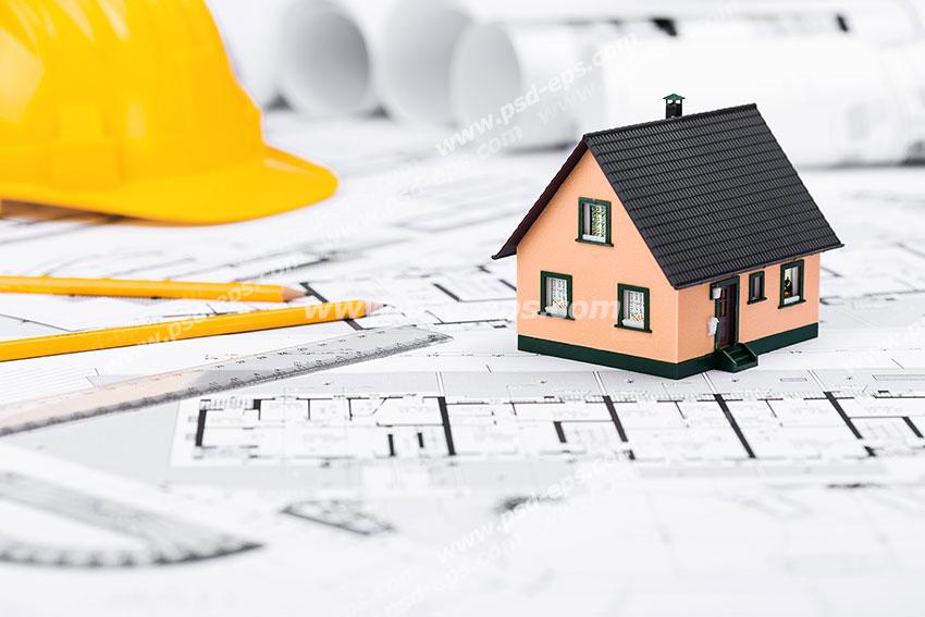 عکس با کیفیت ماکت خانه به همراه کلاه ایمنی و مداد نقشه کشی بر روی پلان های نقشه کشی