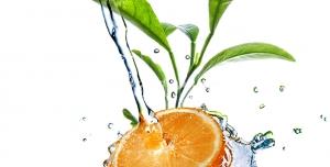 عکس با کیفیت برخورد آب با تکه ای پرتقال در کنار برگ های پرتقال