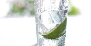 عکس با کیفیت لیوان بلور حاوی تکه یخ ، تکه های لیموی برش خورده و برگ های نعنا