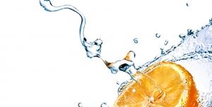 عکس با کیفیت ریزش آب به شکل موج و برخورد آن با تکه ای پرتقال