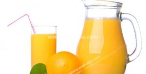 عکس با کیفیت پارچ و لیوان بلور حاوی آب پرتقال به همراه پرتقالی در کنار آن