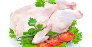 عکس با کیفیت گوشت مرغ کامل خام تزئین شده با کرفس و گوجه