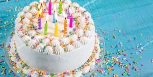 عکس با کیفیت کیک کوچک خامه ای تزئین شده با قیف و ماسوره و شمع و دانه های شکلات رنگی