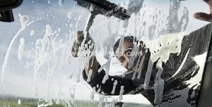 عکس با کیفیت شستشوی شیشه جلوی خودرو توسط کارگر کارواش