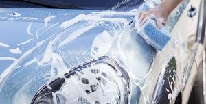 عکس با کیفیت شستشوی خودرو توسط کارگر کارواش با ابر پر از کف مواد شوینده