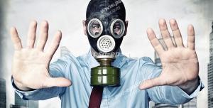عکس با کیفیت مردی در شهری با هوای آلوده با ماسک شیمیایی در حال نشان دادن علامت Stop با دستانش