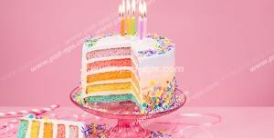 عکس با کیفیت کیک چند لایه میوه ای و مزین با دانه های شکلاتی و شمع