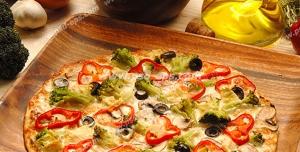 عکس با کیفیت پیتزای نازک ایتالیایی با ظرف چوبی بامبو بر روی میز آشپز در کنار مواد اولیه