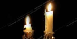 عکس با کیفیت دو عدد شمع روشن بر روی جاشمعی با زمینه مشکی