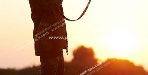 عکس با کیفیت شکارچی در چمنزار با تفنگ شکاری در دست در حال شکار پرنده هنگام غروب آفتاب