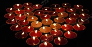 عکس با کیفیت شمع های فانتزی وارمر قرمز و زرد رنگ چیده شده به شکل قلب