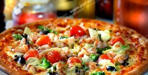 عکس با کیفیت نمای نزدیک از پیتزای گوشت و مرغ با گوجه گیلاسی بر روی میز