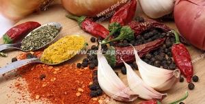 عکس با کیفیت پیازها و سیر و فلفل قرمز و انواع ادویه ها بر روی میز چوبی