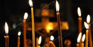 عکس با کیفیت نمای نزدیک از شمع های بلند و ساده روشن در کلیسا با زمینه صلیب