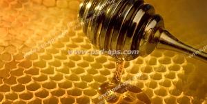 عکس با کیفیت قاشق پر از عسل استیل در حال برداشتن عسل از موم آن