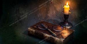 عکس با کیفیت کتاب ، خودکار و عینک در روشنایی نور شمع