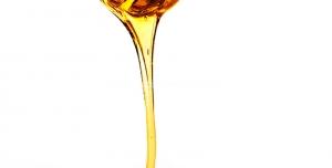 عکس با کیفیت برداشتن عسل با قاشق استیل مخصوص عسل