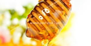 عکس با کیفیت قاشق مخصوص پر از عسل از تکه ای موم عسلی