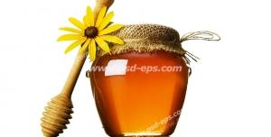 عکس با کیفیت شیشه عسل در کنار قاشق مخصوص عسل و گل بابونه